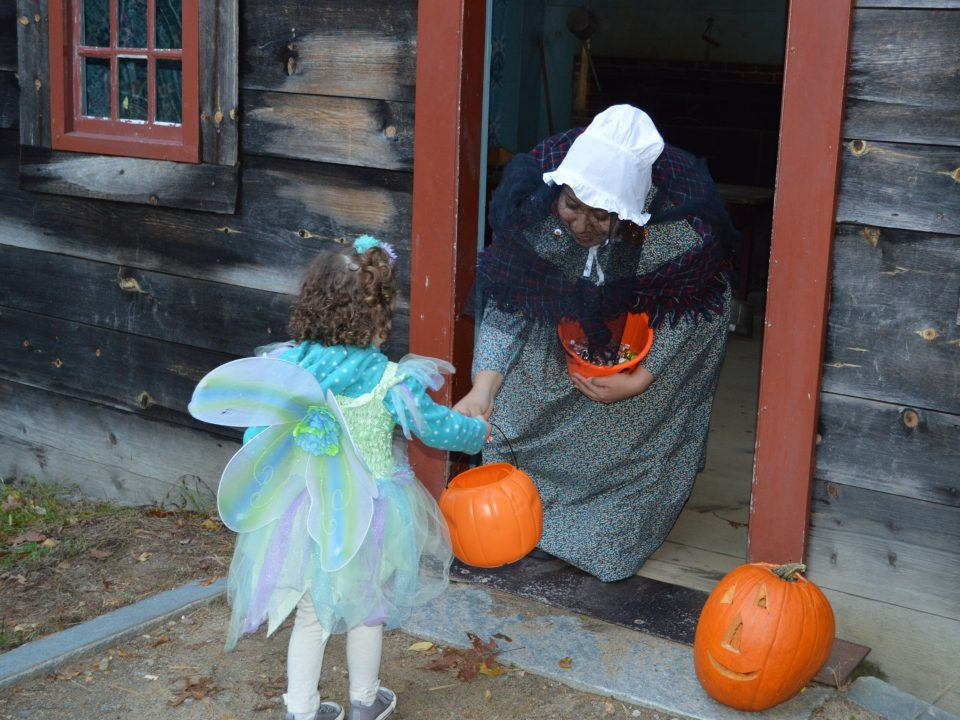 A young girl trick or treating at the Small Hosue
