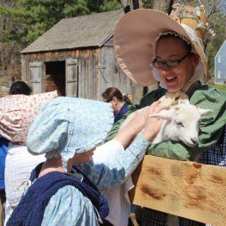 Two girls pet a baby lamb