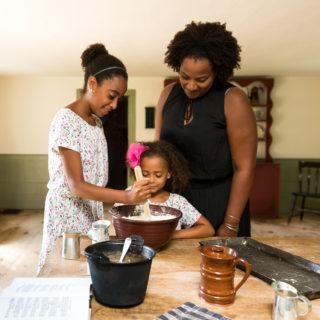 A mom and two kids visit one of the kitchens at Old Sturbridge Village