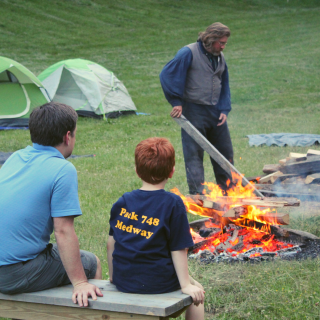 A father and son sit by the bonfire with tents in the background