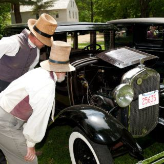 2 Costumed historians look at an antique car