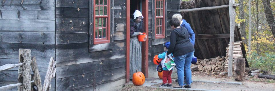 A boy trick or treats at the Small House