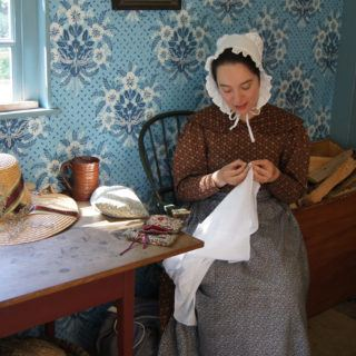 A costumed historian sewing in the small house