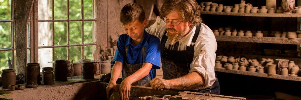 A boy interacts with a Costumed Historian Potter at Old Sturbridge Village