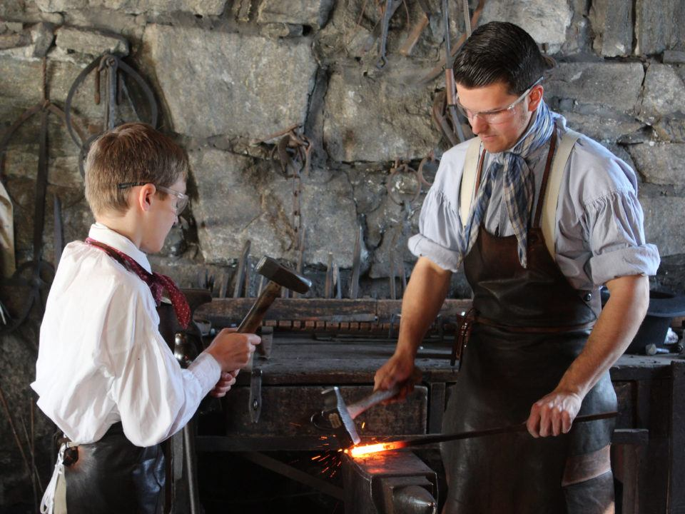 A Discovery Adventures Camper works with a Costumed Historian in the Blacksmith Shop