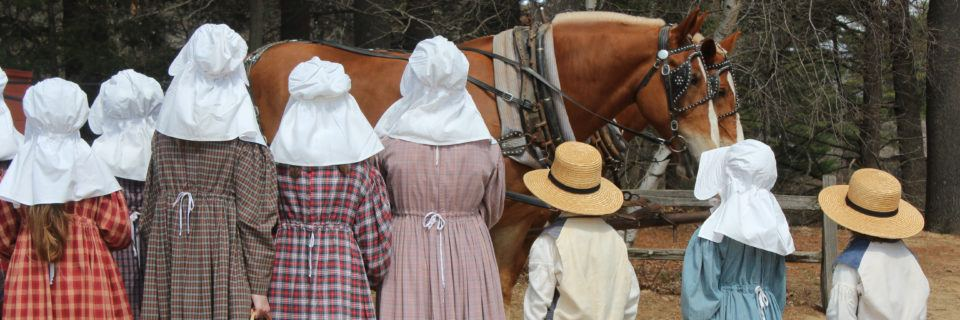 A group of kids in costume waiting for the horse-drawn wagon