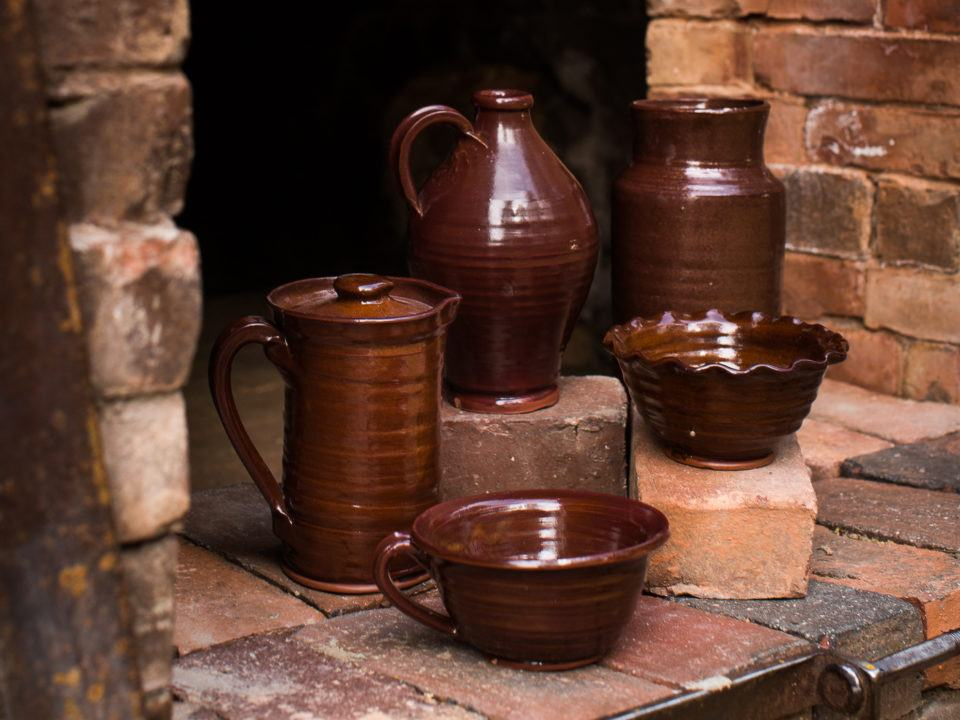 Village-made redware includes mugs, ruffled dishes, covered bean pots, platters and pitchers