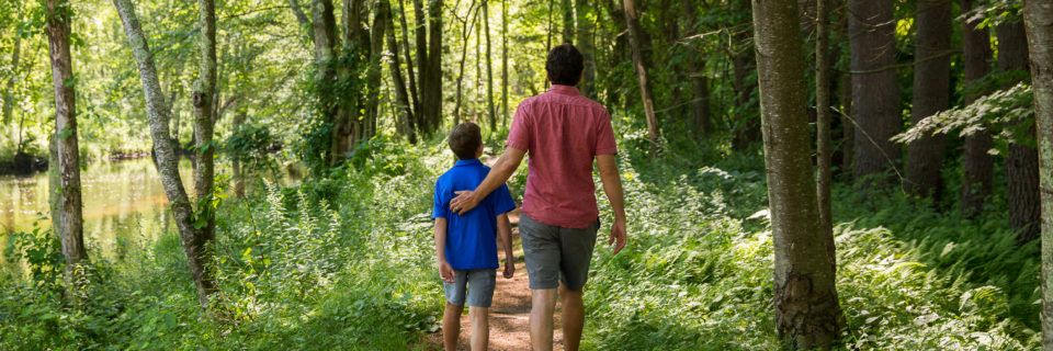 A father and son walk alongside the River at Old Sturbridge Village
