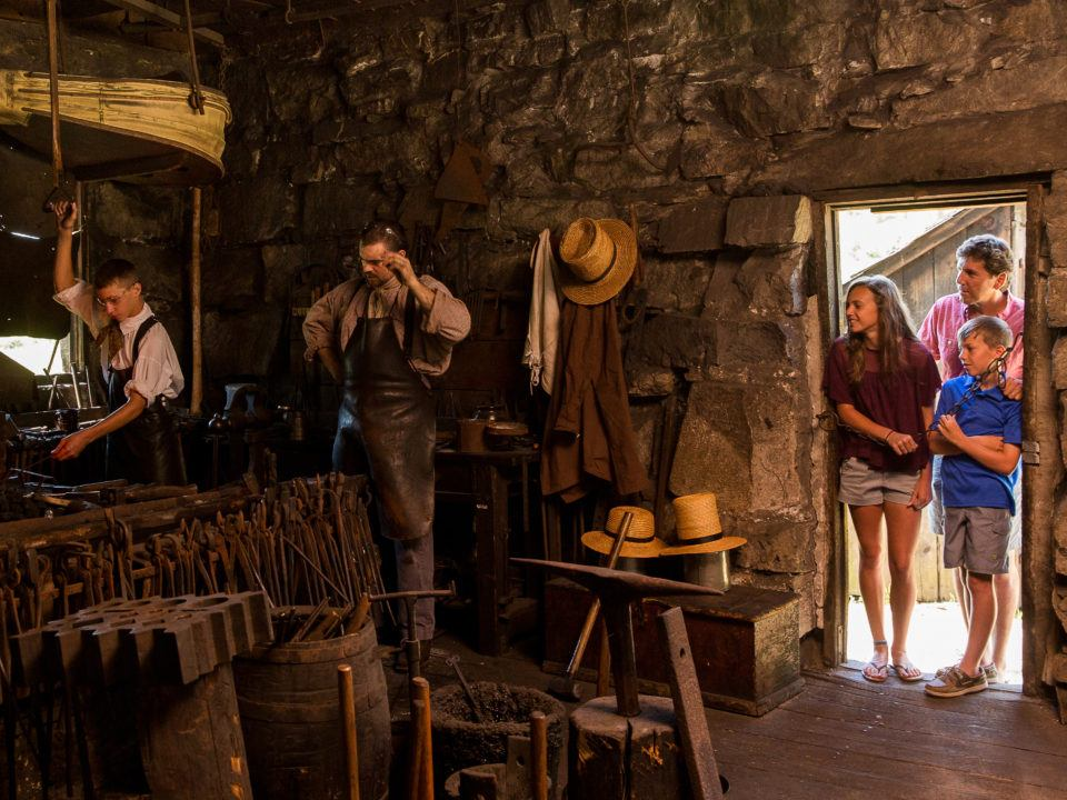 A Family watches the Blacksmiths hard at work