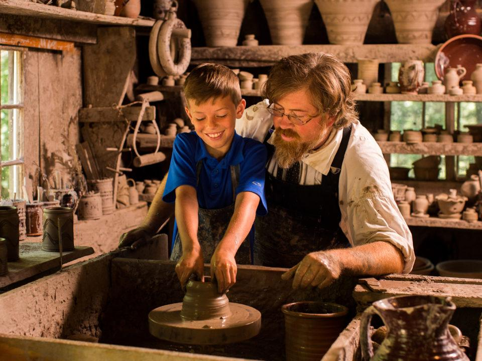 A boy working with a Costumed Historian in the Pottery Shop