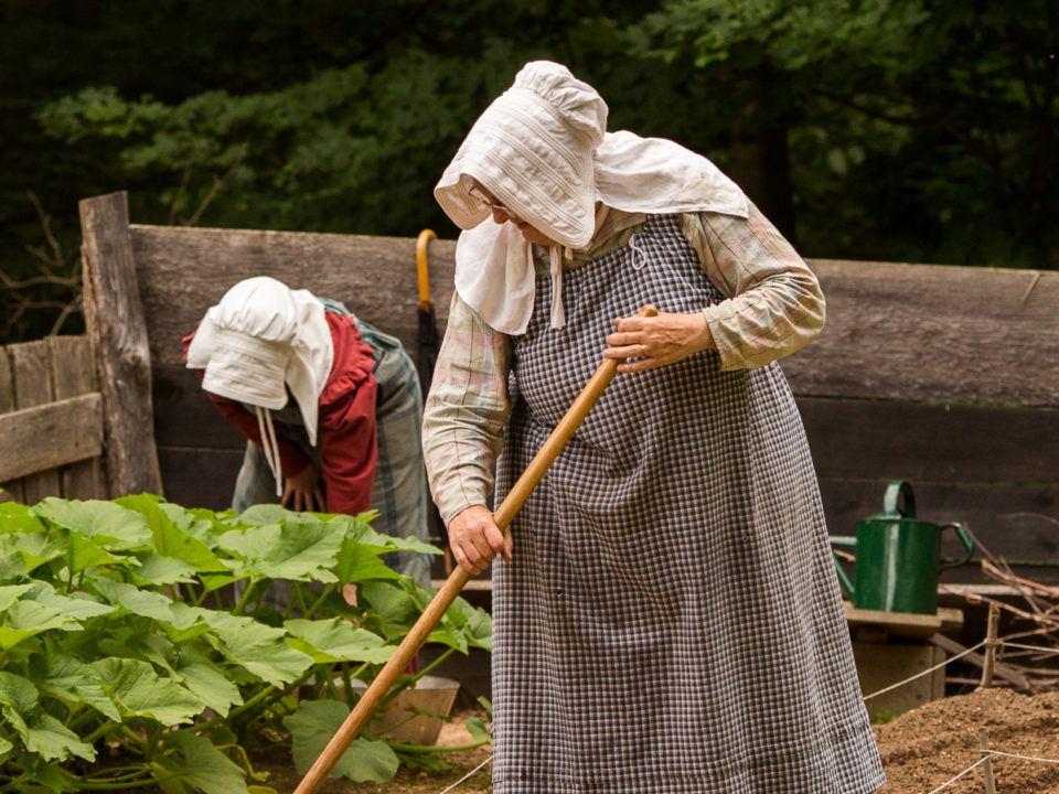 2 costumed historians work in the garden
