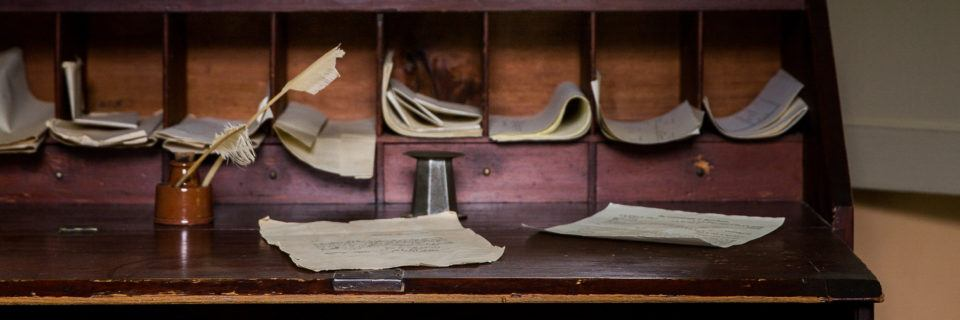 A desk with notes, papers, and quill pens