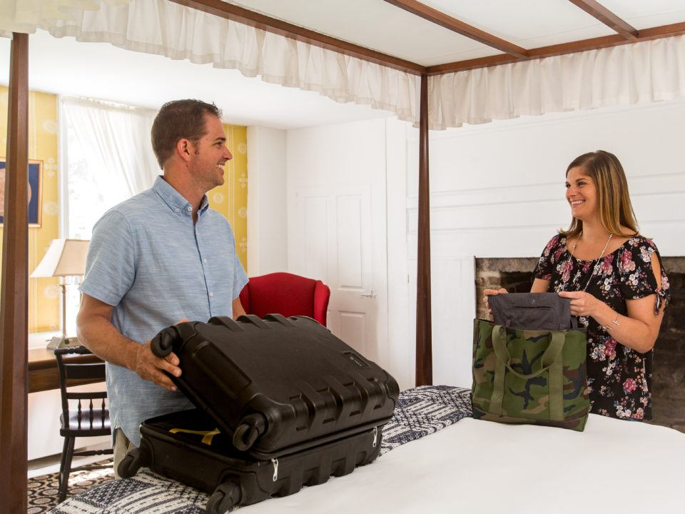 A couple settles down in their room and unpacks their luggage