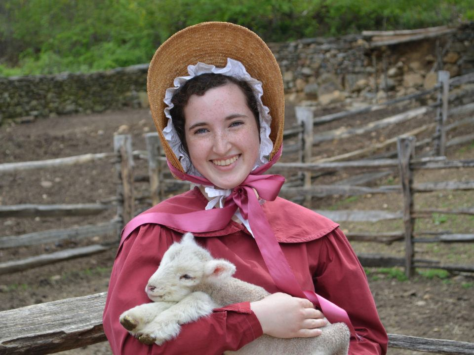 A female Junior Intern in historical costume holds a lamb