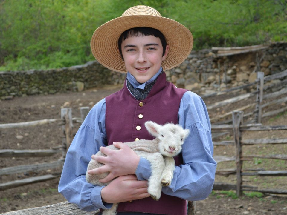 A male Junior Intern in historical costume holds a lamb