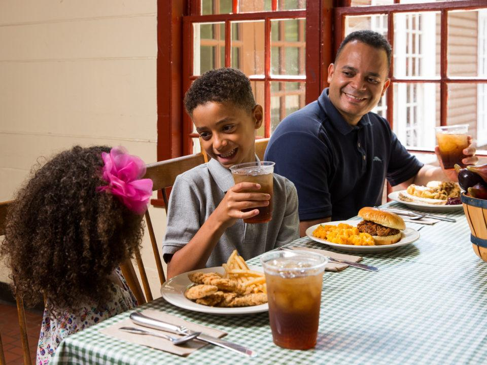 A dad and his kids eat in the Bullard Tavern