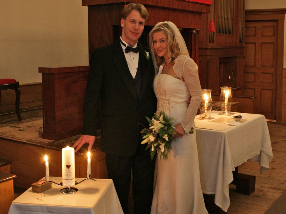A newly married couple in the candlelit Center Meetinghouse