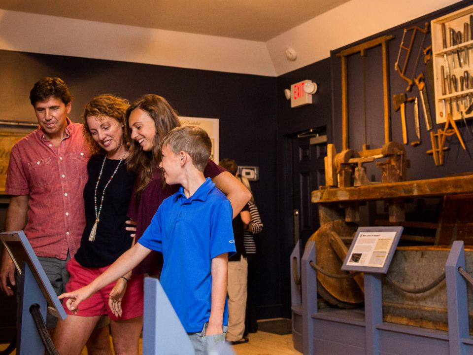 A family visits the Cabinet Making Exhibit