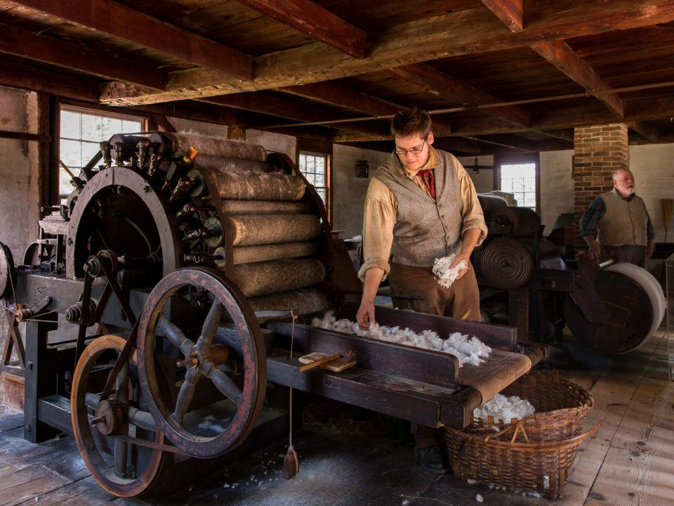 A costumed historian works the Carding Mill
