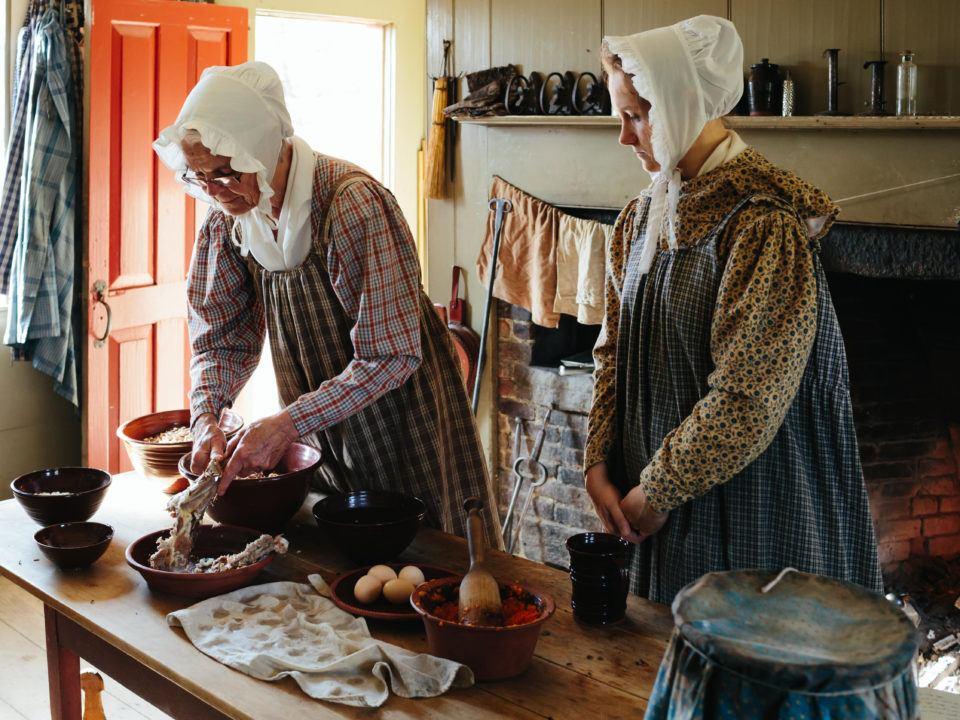 2 costumed historians cooking in the Freeman Kitchen