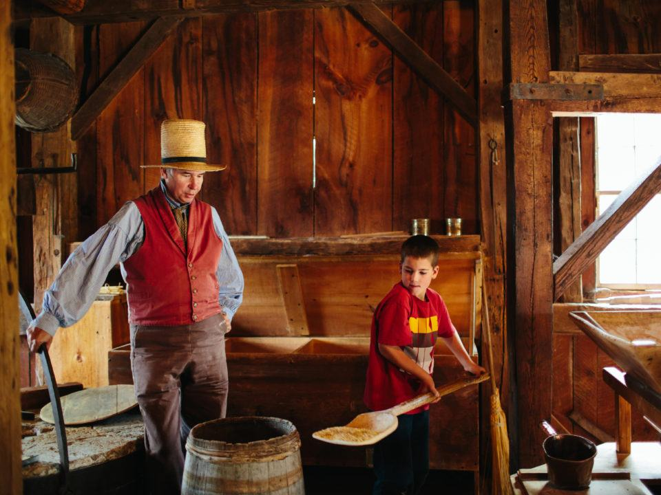 A boy and a costumed historian in the Grist Mill