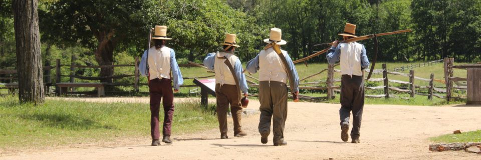 Four farmers in historical costume head out to the fields with their tools in tow