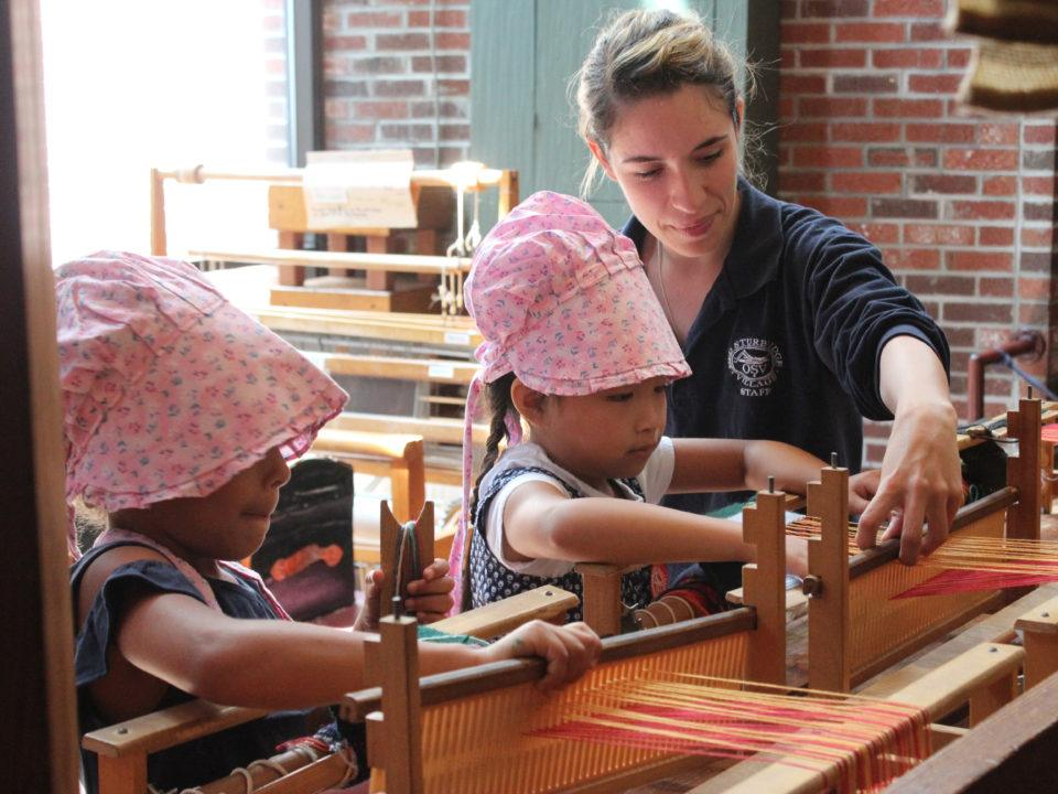 Two young girls learn how to weave on looms under the guidance of a Museum Educator
