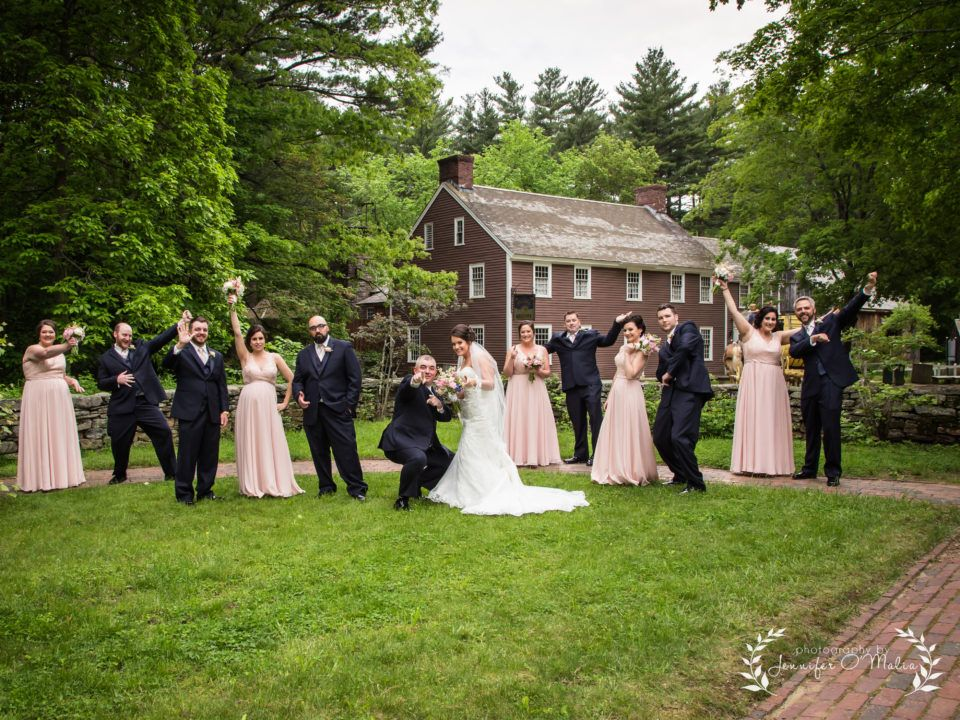 A bride and groom with their wedding party poses for the camera in the Salem Towne Garden