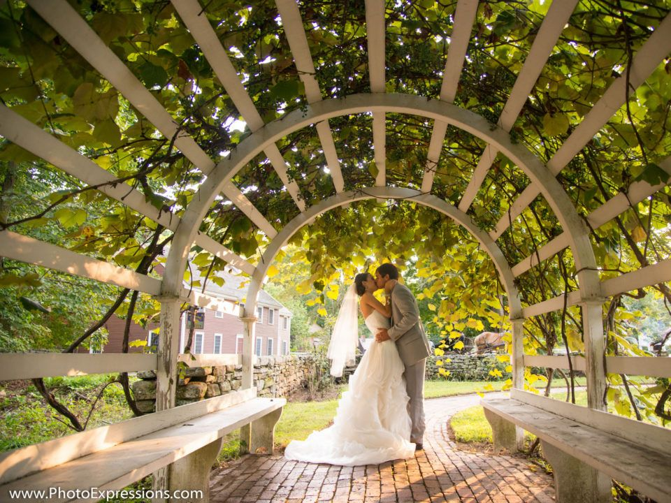 A newly married couple kiss and embrace under the arbor in the Salem Towne Garden