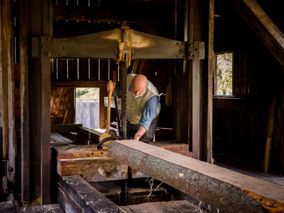 A costumed historian works in the Sawmill