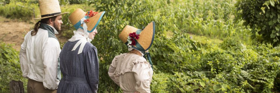 3 individuals dressed in early 19th-century costume outside at Old Sturbridge Village