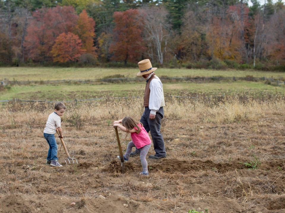 Two kids and a costumed historian working in the fields
