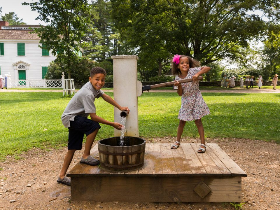 Two kids trying out the Water Pump