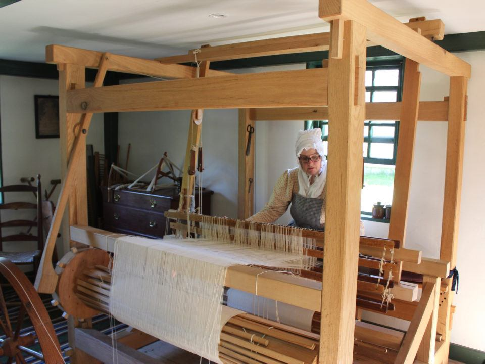 A costumed Historian Weaving in the Fenno House