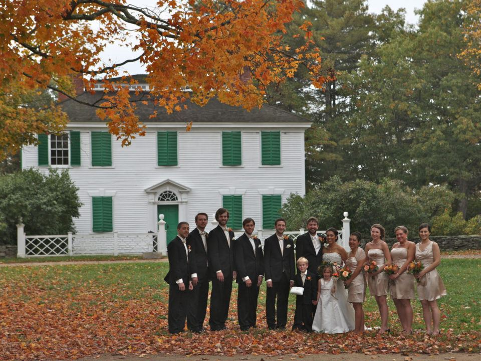A bride and groom with their bridesmaids and groomsmen line up in front of the Salem Towne House in fall