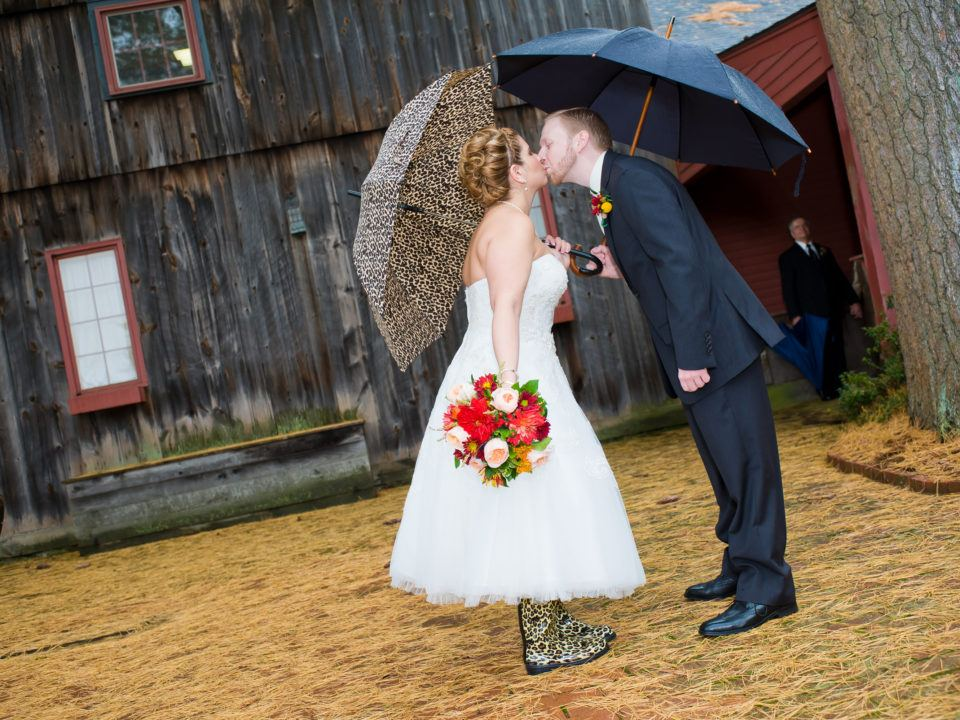 A newly married couple kiss in the rain while holding umbrellas