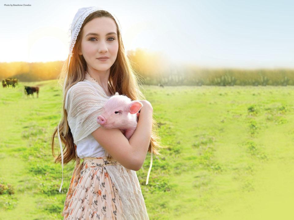 A young girl holds a baby pig