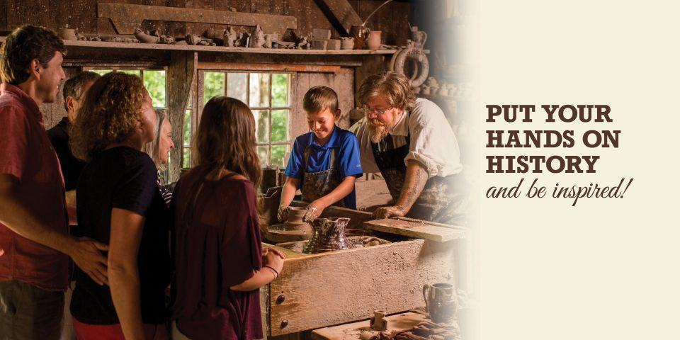 A young visitor tries his hand at the potter's wheel as his family watches