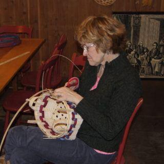 A woman weaves a basket