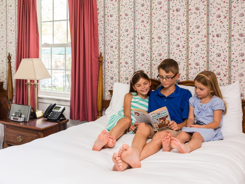 Three kids reading on a bed in the Lodges