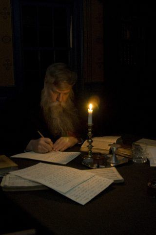 A man works on writing by candlelight