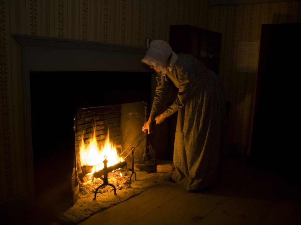 A woman tends the fire