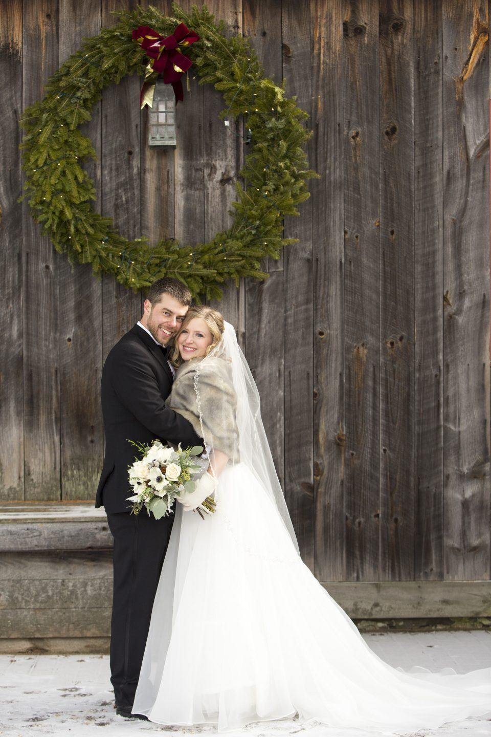 A bride and groom pose outside in front of a large wreath