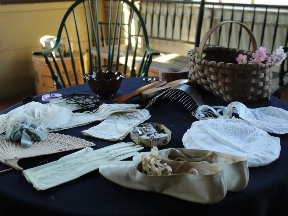 Shoes, a fan, hair accessories, and more displayed on a table