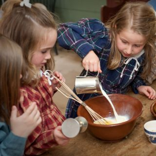 Young girls in costume cooking