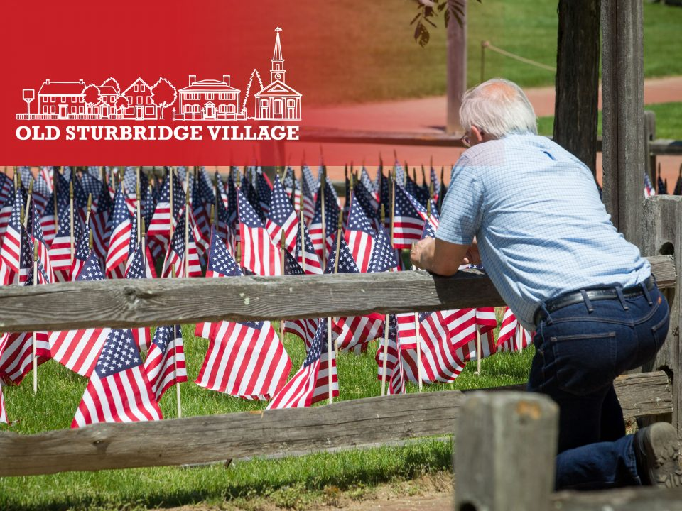 A man kneels and looks at the Field of Flags at OSV