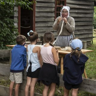 4 kids visit with a costumed historian processing wool