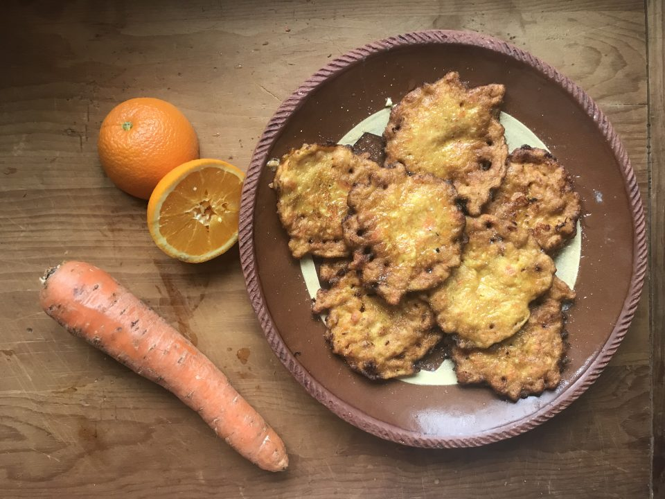 Finished carrot fritters on a plate with a carrot and orange on the side