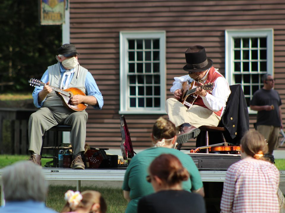 Two men in 1830s costumed play music on the Village Common
