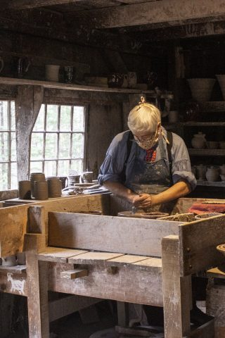 A potter makes a pot in the Pottery Shop